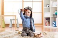 使用与在地板上的木玩具飞机的愉快的儿童男孩在托儿所屋子里 免版税库存图片