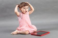 使用与在地板上的片剂计算机的女孩 免版税库存图片
