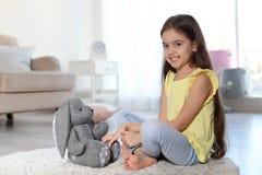 使用与在地板上的玩具兔宝宝的逗人喜爱的小孩户内 库存照片