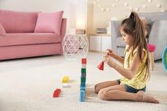 使用与在地板上的积木的逗人喜爱的小孩 免版税库存照片