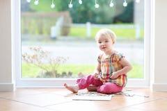 使用与在地板上的难题的学龄前儿童女孩 免版税库存照片