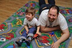 使用与在地毯的玩具的儿子和父亲 免版税图库摄影