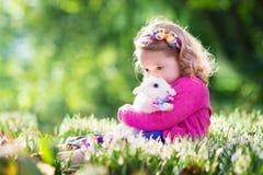使用与在复活节彩蛋狩猎的兔宝宝的小女孩 免版税库存照片