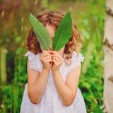 使用与在夏天森林自然探险的叶子的儿童女孩与孩子 库存图片