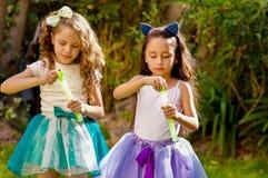 使用与在夏天自然的肥皂泡的两个愉快的美丽的小女孩,一个女孩佩带一只蓝色耳朵老虎 免版税库存照片