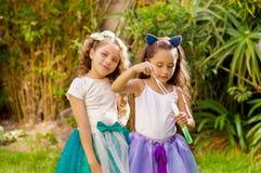 使用与在夏天自然的肥皂泡的两个愉快的美丽的小女孩,一个女孩佩带一只蓝色耳朵老虎 免版税库存图片