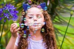 使用与在夏天自然,佩带的肥皂泡的愉快的矮小的卷曲女孩老虎辅助部件的蓝色耳朵在她的 免版税库存图片