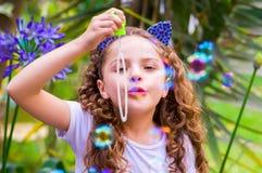 使用与在夏天自然,佩带的肥皂泡的愉快的矮小的卷曲女孩老虎辅助部件的蓝色耳朵在她的 免版税库存照片