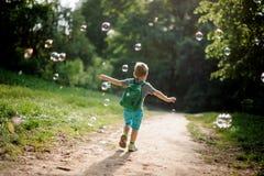使用与在夏天pa的肥皂泡的后面观点的一个小男孩 图库摄影