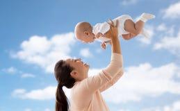 使用与在天空的小男婴的愉快的母亲 免版税库存照片