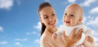 使用与在天空的小男婴的愉快的母亲 库存图片