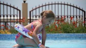 使用与在室外游泳池的五颜六色的可膨胀的圆环的愉快的小女孩在热的夏日 孩子学会游泳 影视素材
