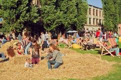 使用与在干草的家庭的未认出的孩子以室外城市节日为基础 免版税库存图片