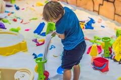 使用与在幼儿园的沙子的男孩 美好的马达概念的发展 创造性比赛概念 免版税库存图片