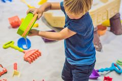 使用与在幼儿园的沙子的男孩 美好的moto的发展 库存照片