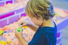 使用与在幼儿园的运动沙子的男孩 美好的马达概念的发展 创造性比赛概念 免版税库存照片