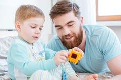 使用与在床上的玩具的爸爸和儿子 免版税库存照片