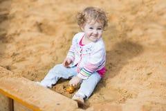 使用与在操场的沙子的滑稽的女婴 库存图片