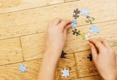使用与在木地板上的难题的小孩与父母,生活方式人概念,对其中每一的爱恋的手一起 库存照片