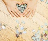 使用与在木地板上的难题的小孩与父母,生活方式人概念,对其中每一的爱恋的手一起 免版税库存照片