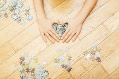 使用与在木地板上的难题的小孩与父母,生活方式人概念,对其中每一的爱恋的手一起 免版税库存图片
