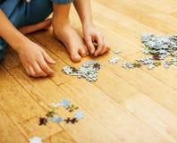 使用与在木地板上的难题的小孩与父母,生活方式人概念,对其中每一的爱恋的手一起 免版税图库摄影