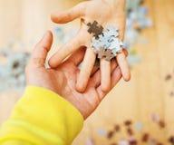 使用与在木地板上的难题的小孩与父母,生活方式人概念,对其中每一的爱恋的手一起 图库摄影