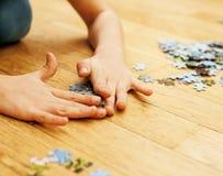 使用与在木地板上的难题的小孩互相一起做父母,生活方式人概念,爱恋的手 库存照片