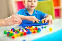 使用与在桌上的教育玩具的男孩 库存图片