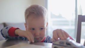 使用与在桌上的玩具汽车的哀伤的孤独的小男孩 股票视频