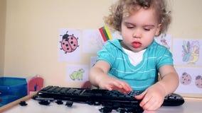 使用与在桌上的键盘钥匙的逗人喜爱的小孩女孩 股票录像