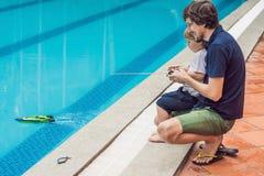 使用与在水池的一条遥控小船的父亲和儿子 库存照片