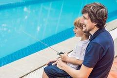 使用与在水池的一条遥控小船的父亲和儿子 图库摄影