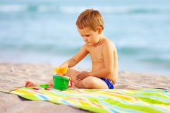 使用与在沙子的玩具的逗人喜爱的孩子在海滩 免版税库存图片