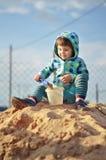 使用与在沙盒的沙子的逗人喜爱的女婴 免版税库存图片