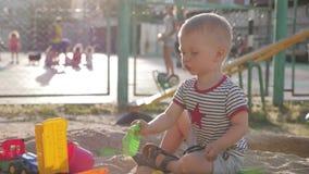 使用与在沙盒的玩具的小男孩在日落 影视素材