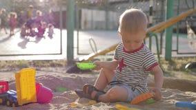 使用与在沙盒的玩具的小男孩在日落 股票录像