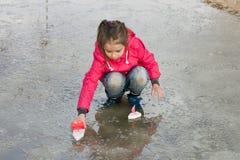 使用与在泉水水坑的手工制造船的雨靴的愉快的逗人喜爱的小女孩 库存图片