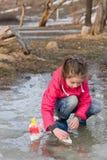 使用与在泉水水坑的手工制造船的雨靴的秀丽小女孩 库存照片