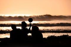 使用与在海滩的一个球的年轻朋友剪影在日落 免版税库存图片