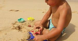 使用与在海滩的沙子的庄稼孩子 股票视频