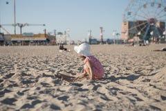 使用与在海滩的沙子的小女孩 免版税库存照片