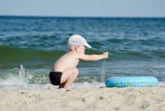使用与在海滨的沙子的小白肤金发的男孩 免版税库存图片