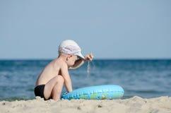 使用与在海滨的沙子的小白肤金发的男孩 免版税库存照片