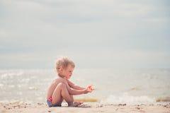 使用与在海滩的沙子的逗人喜爱的小女孩 免版税库存图片