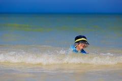 使用与在海滩的波浪的小男孩 库存图片