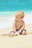 使用与在海滩的海壳的孩子滑稽的画象 免版税图库摄影