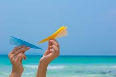 使用与在海滩的纸飞机的女性手 免版税库存照片