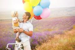 使用与在淡紫色领域的气球的父亲和儿子 库存图片