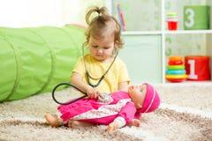 使用与在游戏室的一个玩偶的儿童女孩 免版税图库摄影